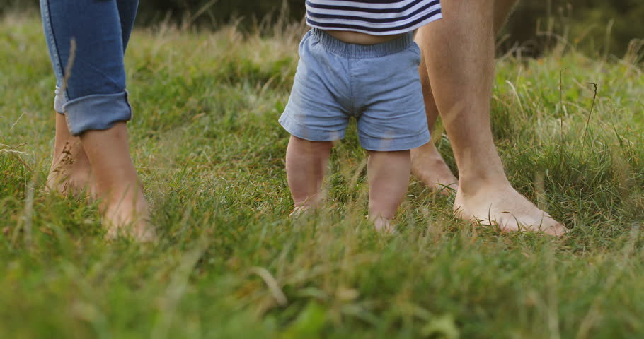 Close up of the first steps of the baby while holding hands of mother and father from bothe sides on the green grass. Caucasian barefeet. Outside.