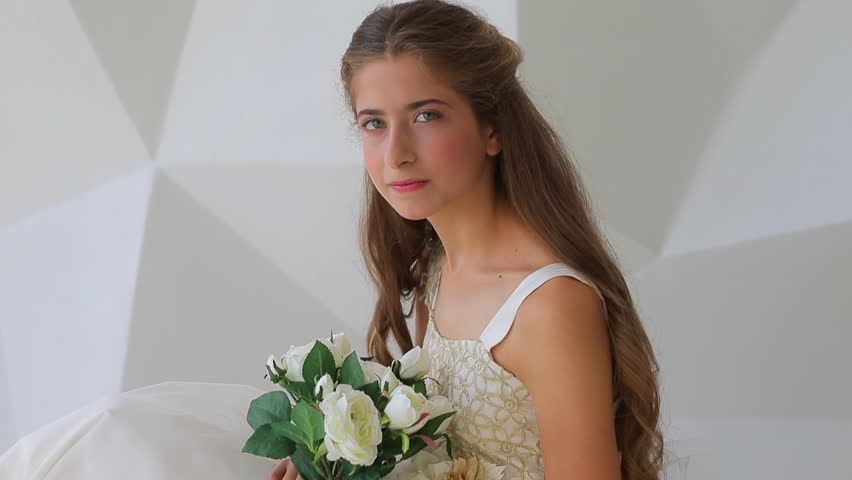 Young model girl 12 y.o. dressed in white clothes with flowers in photo shooting process. Beautiful eyes, long hair styled. Reproductive system andteens health concept.