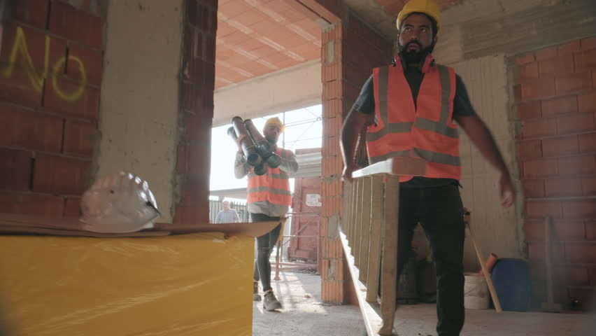 People working in construction site. Men at work in new house inside apartment building. Team of professional workers using tools and equipment