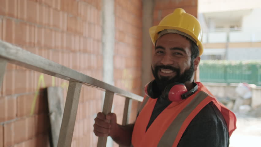 Confident people working in construction site. Portrait of happy hispanic man at work in new house inside apartment building. Professional latino worker using ladder and smiling at camera. Slow motion