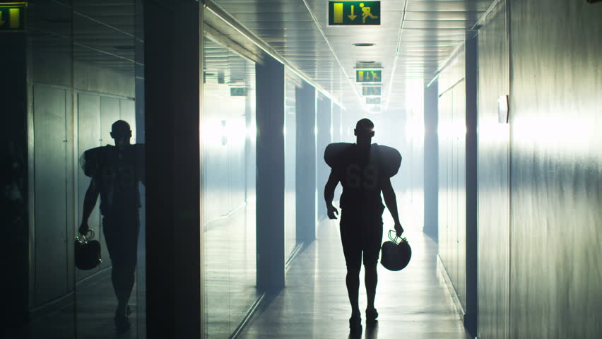 4K American football player walks alone through stadium tunnel before or after a game #10194215