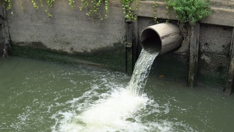 Drain polluted sewage in channel at city street, zoom in view