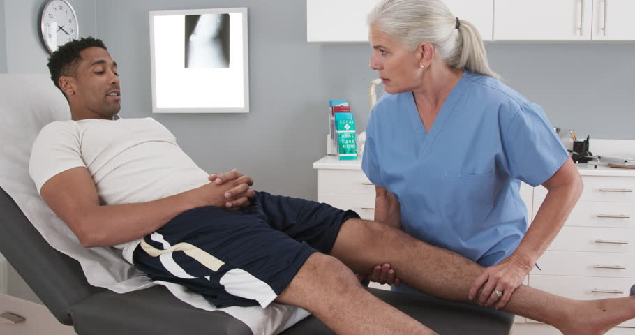 Male millennial black patient at clinic with injured knee assisted by senior doctor. Female Physical therapist or assessing male athletes leg injury