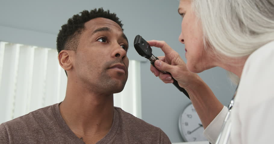 Young black male patient having his eyes checked by senior female doctor. Mature female doctor using ophthalmoscope to examine eyes of african-american patient