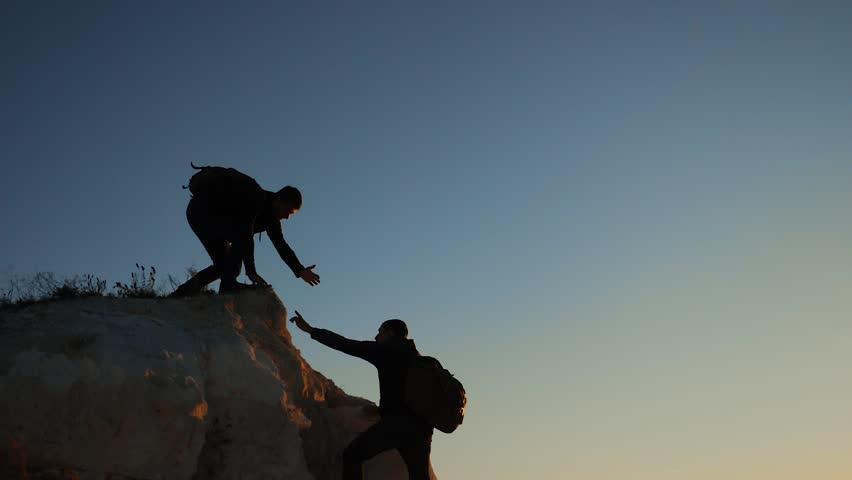 Silhouette hiker man tourists hands help climber climbs a mountain. walking tourist hiking adventure climbers sunset climb the mountain . slow motion video. hiker sunlight on top win victory the hill | Shutterstock HD Video #1019465638