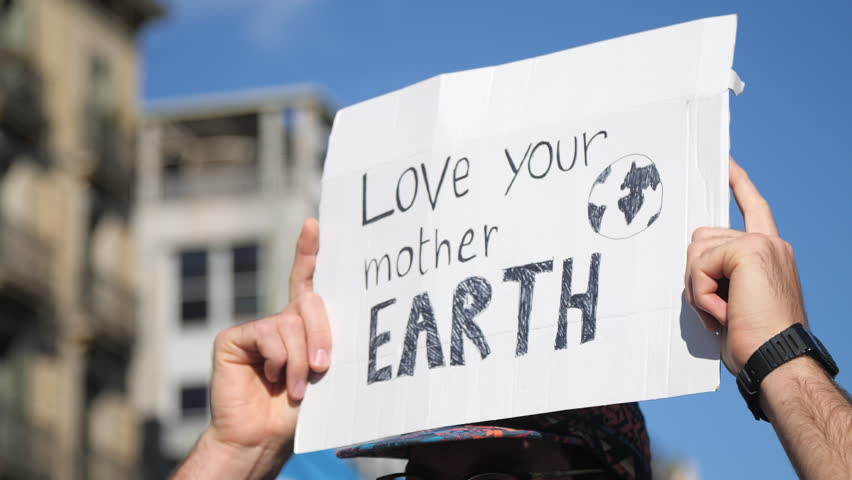 """Love your Mother Earth"" Poster on a Demonstration due to Climate Change. Activism against capitalism. Strong message on a march.  