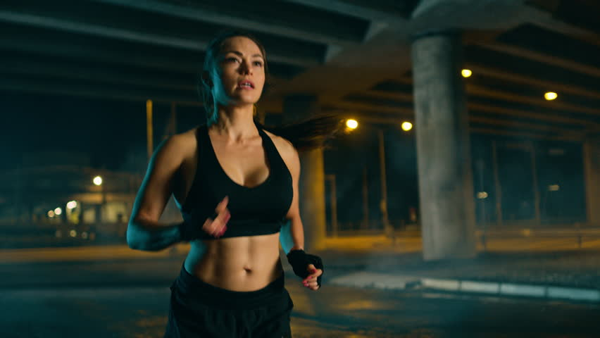 Beautiful Busty Fitness Girl in Black Athletic Top and Shorts is Jogging on the Street. She is Doing a Workout in a Night Urban Environment Under a Bridge with Cars in the Background.