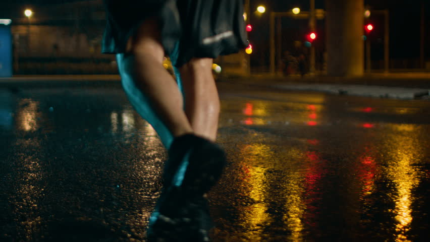Close Up Leg Shot of an Athletic Young Man in Sports Outfit Jogging in a Rainy Street. He is Running in a Dark Urban Environment Under a Brindge with Cars in the Background.