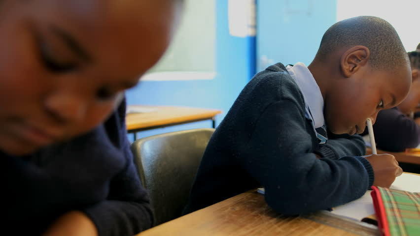 Side view of African American thoughtful schoolboy studying in the classroom at school  | Shutterstock HD Video #1019499994