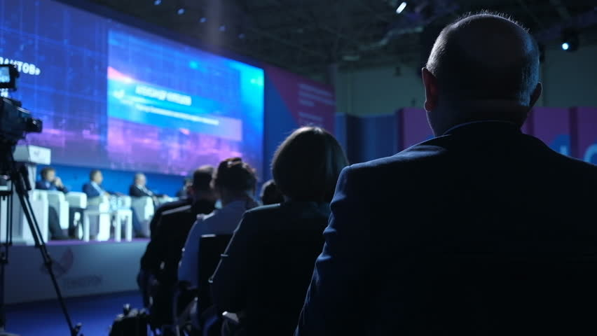 People on the forum on business development. The audience. Hall is full. Audience listens to the speech in the conference hall. International economic business forum. Back view. Royalty-Free Stock Footage #1019501275
