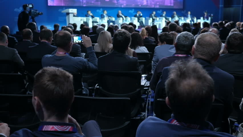 People on the forum on business development. Hall is full. View from the back of auditorium with people at a conference or presentation, master class. International economic business forum Royalty-Free Stock Footage #1019501278