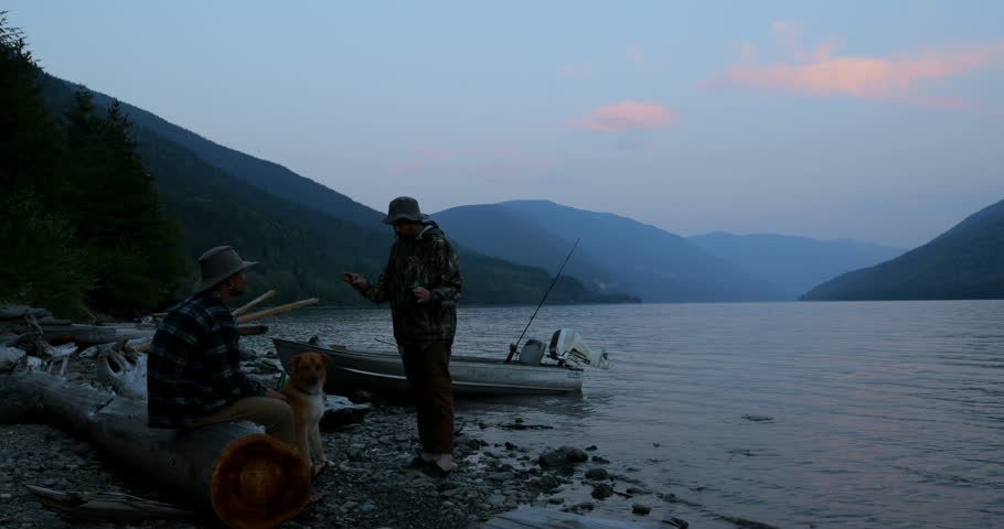 Two fishermen interacting with each other near riverside at dusk 4k | Shutterstock HD Video #1019507851