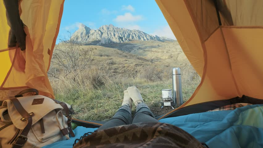 Camping woman lying in tent Close up of Girl feet wearing hiking boots relaxing on vacation. From the tent view of the big mountains. Hiking lifestyle during summer. Traveling alone in the mountains #1019520139