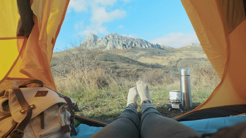Camping woman lying in tent Close up of Girl feet wearing hiking boots relaxing on vacation. From the tent view of the big mountains. Hiking lifestyle during summer. Traveling alone in the mountains #1019520160