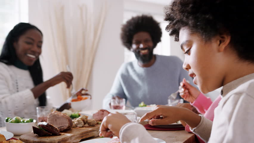Tween black boy sitting at the dinner table eating Sunday lunch with his family, side view, selective focus | Shutterstock HD Video #1019528164