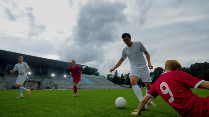 Professional Soccer Player Leads with a Ball, Masterfully Dribbling and Bypassing Sliding Tackles of His Opponents. Two Professional Football Teams Playing. Following Low Angle Shot.