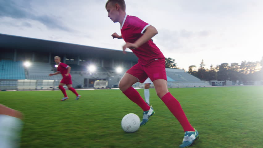 Professional Soccer Player Leads with a Ball, Masterfully Dribbling and Bypassing Sliding Tackles of His Opponents. Two Professional Football Teams Playing Important Match on a Field. | Shutterstock HD Video #1019538181