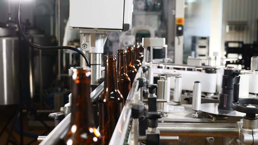 Technological line in brewery. Empty glass bottles on conveyor being transported. Technological process of beer production. 4k   Shutterstock HD Video #1019546401