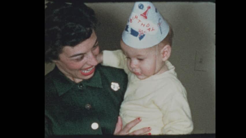 50's Mom lights baby boys 1st birthday cake