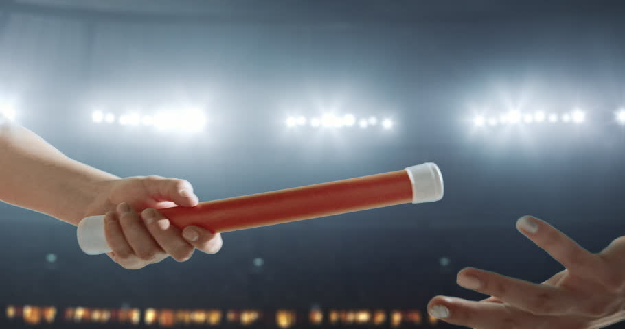 Passing a baton during the relay race on the professional stadium.