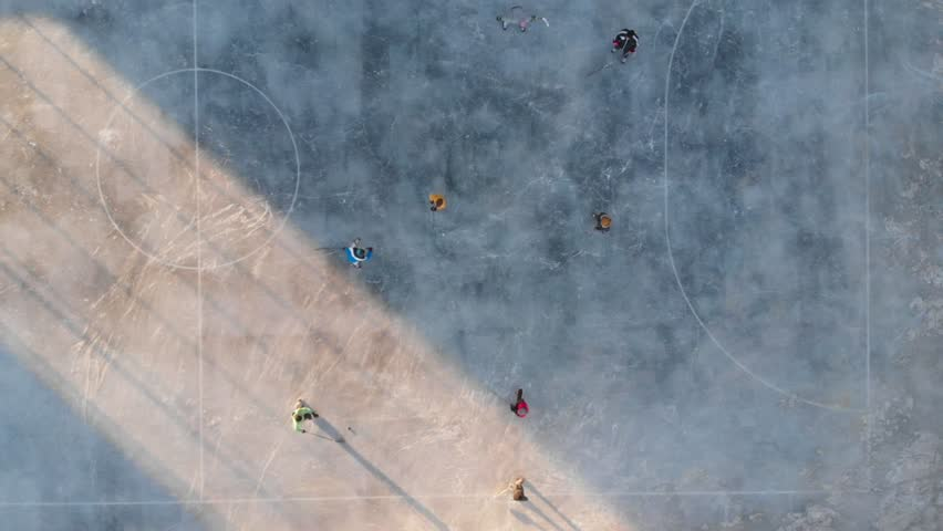 Children playing hockey ice field, aerial video. Ice hockey sport young boys players outdoors. Drone flying over ice hockey players kids.  #1019586070