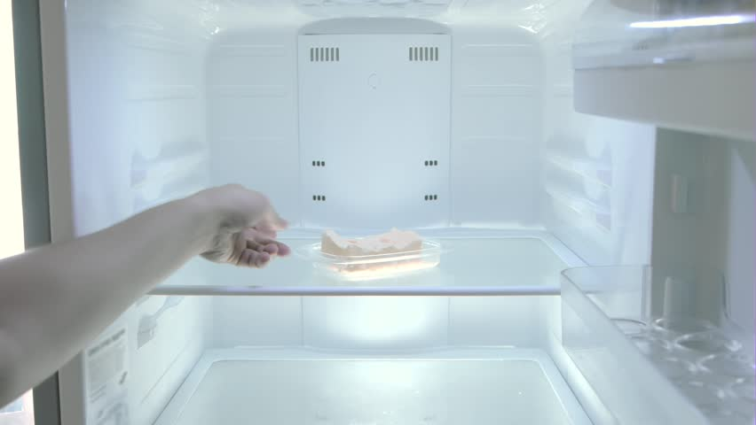 The man opens the empty fridge and slowly takes out butter, bachelor life