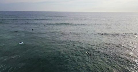 Group of surfers on the surfboards on the ocean waves on the cloudy sky background on Sri Lanka. Aerial video recording with backward motion.