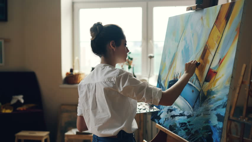 Serious female artist is working at picture using oil paints and palette-knife creating beautiful marine landscape on canvas. Painting technique and painters concept.