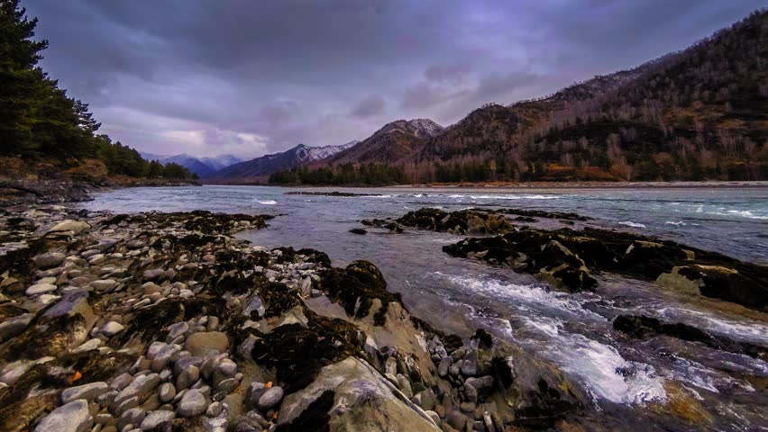 4k UHD timelapse shot of the splashing water in a river near mountain forest. Huge rocks and fast clouds movenings.   Shutterstock HD Video #1019617540
