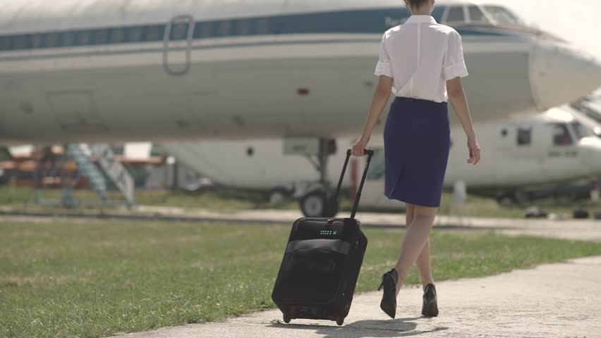 Beautiful and cheerful flight attendant walks towards the airplane. Stewardess with a suicase. Highheal shoes. Sexy flight attendant.