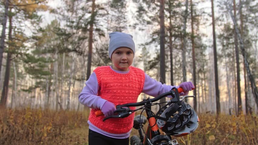 One caucasian children walk with bike in autumn park. Little girl walking black orange cycle in forest. Kid goes do bicycle sports. Biker motion ride with backpack and helmet. Mountain bike hardtail. | Shutterstock HD Video #1019630731