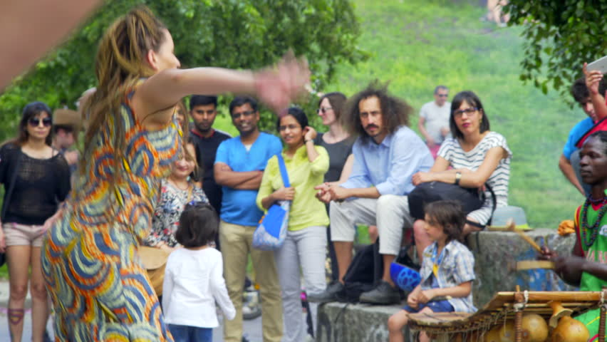 GERMANY - CIRCA JUNE 2017 - White woman dances, African Jamaica drum musician band music, Mauer park, Berlin