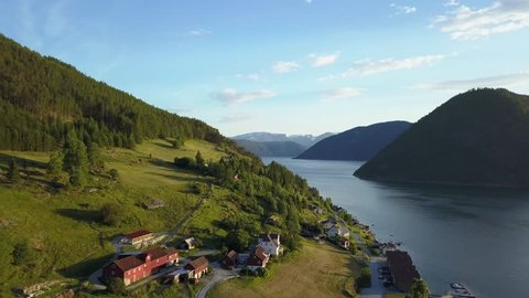 Fjord drone view of green coastline in Norway landscape. Beautiful light over calm sea and hills. Typical, colorful Norwegian summer homes house by the water Sognefjord. Aerial shot in summer evening
