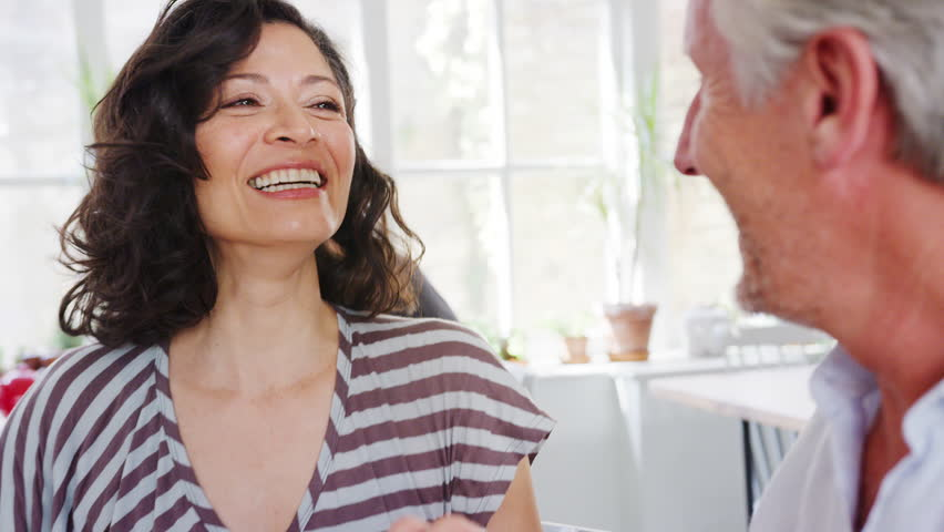 Middle aged Hispanic woman talking with her senior male friend, close up