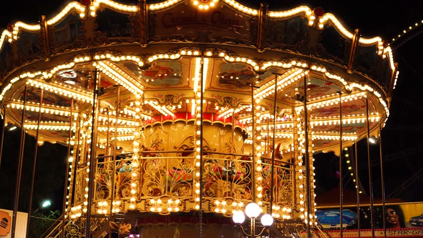 Incredible colorful flashing light of vintage carousel carnival fair merry go round circus horse ride at amusement park