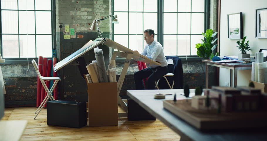 Architect man sits at drafting table in modern industrial office during the day. Wide to long shot on 4K RED camera on a gimbal.