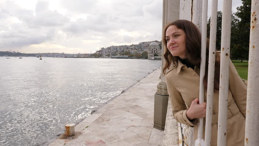Woman look out to Bosphorus strait, squeeze out between bars of old fence at embankment, turn head and wondering of nice view. Portrait of happy tourist walking around Istanbul city, discovering sight | Shutterstock HD Video #1019683876