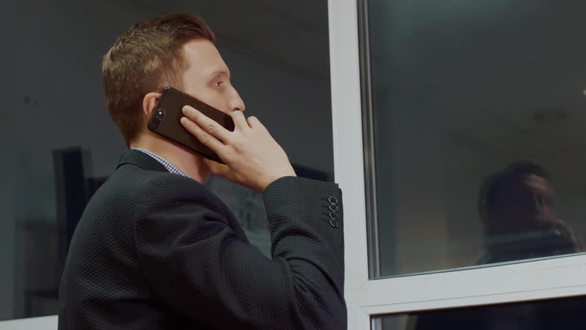 Closeup view from back of man looking through window while having mobile call on cell phone evening office | Shutterstock HD Video #1019695456