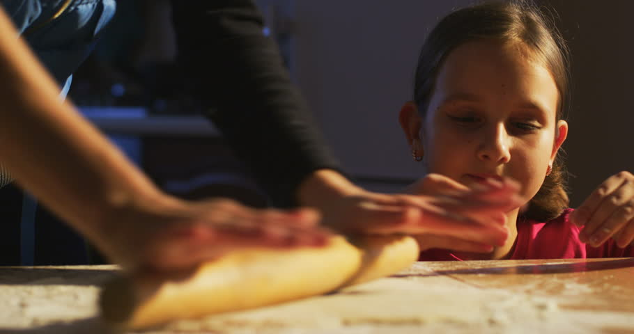Portrait of Little Kid Looking at Mother who is rolling the dough and teaching daughter to cook learning and preparing food for family dinner in the Kitchen indoors shot on RED camera #1019730823