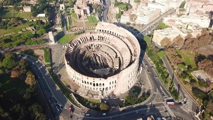 Aerial drone view video of iconic ancient Arena of Colosseum, also known as the Flavian amphitheatre in the heart of Rome, Italy