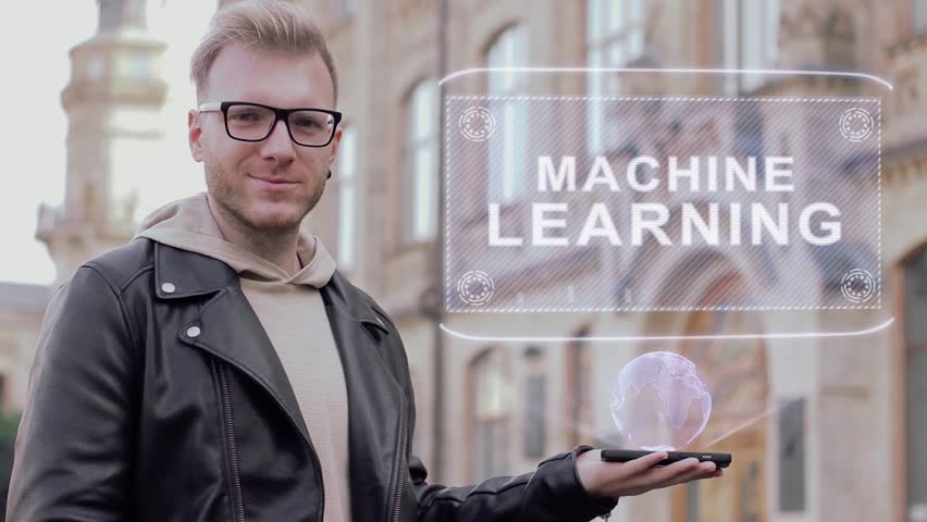 Smart young man with glasses shows a conceptual hologram Machine Learning. Student in casual clothes with future technology mobile screen on university background