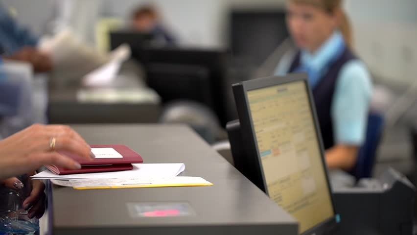 Airport employee checking passport of people passengers on border and selling tickets in airport counters. check-in on board aircraft, close up, close-up, Checking passports at the airport check in.