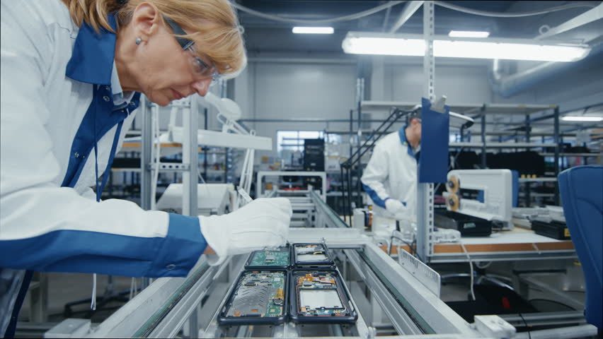 Time Lapse of Electronics Factory Workers Assembling Smartphone Circuit Boards by Hand While they Move on the Assembly Line. High Tech Factory Facility.  Royalty-Free Stock Footage #1019784457