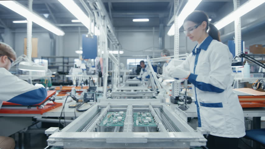 Time Lapse of Electronics Factory Workers Assembling Circuit Boards by Hand While it Moves on the Assembly Line. High Tech Factory Facility.