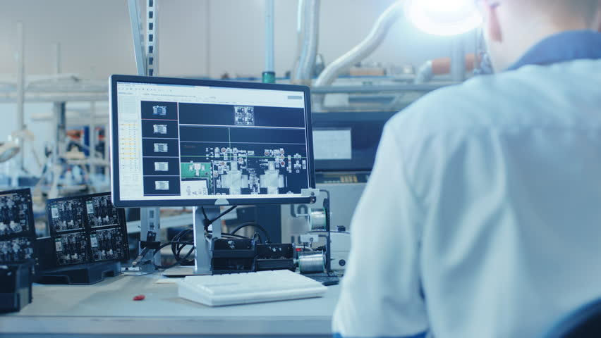 Electronics Factory Worker in White Work Coat Inspects a Printed Circuit Board on a Computer Screen that is connected to a Digital Microscope. High Tech Factory Facility. Royalty-Free Stock Footage #1019784475
