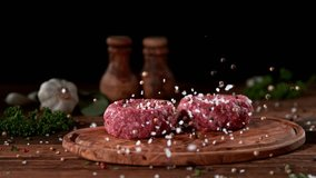 Super slowmotion footage of strewing salt and pepper at fresh raw beef meat burger, 1000fps, 4K