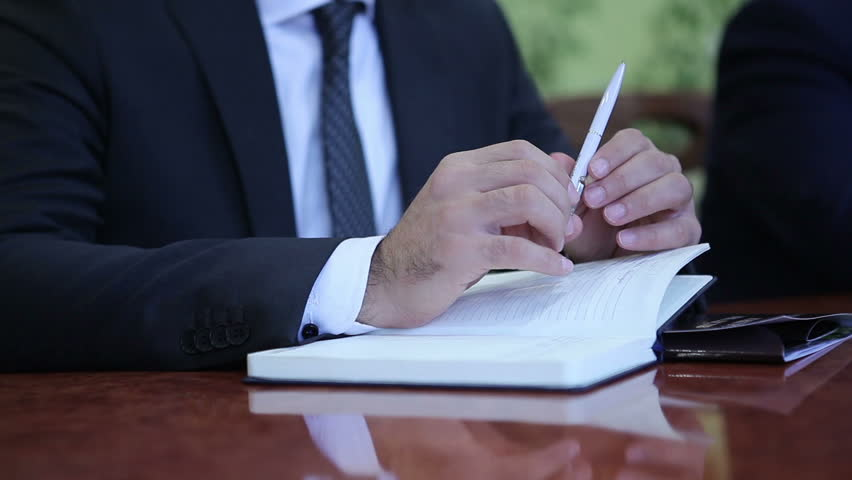 The judicial divorce proceedings. The lawyer writes testimony in court.Male attorney records client information