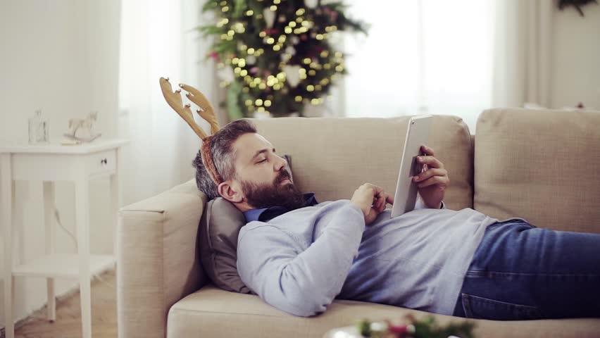 A man with reindeer headband lying on a sofa at Christmas time, using tablet. #1019795767