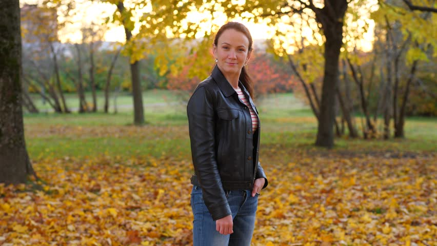 Young adult woman pose in autumn park, turn head and look aside. Pretty lady wear black jacket, half length portrait shot. Blurred background | Shutterstock HD Video #1019802523