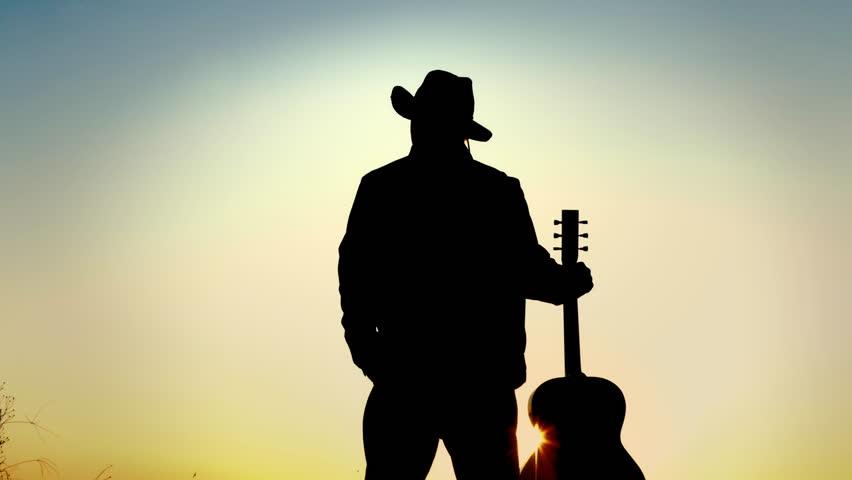 Cowboy man holding guitar at sunset